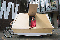 © London News Pictures. 23/06/15. London, UK. Daniel Durnin sits in his design 'WaterBed Mobile Architecture' which is part of the Royal College of Art Graduate Exhibition 2015, Central London. The design is a boat which can be towed by a bike, and also provides sleeping accomodation for two people. Photo credit: Laura Lean/LNP