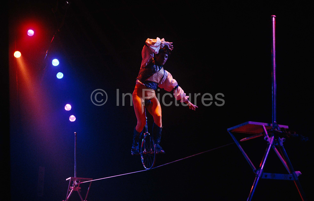 Half-way across the thin taut wire of a tightrope, an tightwire walker acrobat riding a monocycle pauses and wobbles to compensate his balance before continuing his journey across to safety at the other end of two supporting poles The act forms part of the Canadian circus troupe Cirque de Soleil during a show in Battersea, London. Blue and red spotlights illuminate this daredevil and we see his tights, his wide-sleeved theatrical shirt and the concentration and grim determination on his face - the look of a professional trickster at work. He may be showing a seemingly dangerous and unpredictable stunt though in truth, he will have rehearsed this simple balancing act for many years but must still keep up the illusion of danger for the sake of a gasping, gullible audience.