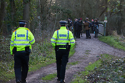 Denham, UK. 3 February, 2020. Police officers monitor environmental activists from Extinction Rebellion, Save Colne Valley and Stop HS2 occupying a bridge in Denham Country Park to seek to prevent works for the HS2 high-speed rail link including the felling of 200 trees and the construction of a Bailey bridge, compounds, fencing and a parking area. Part of the location for the work lies within a wetland nature reserve forming part of a Site of Metropolitan Importance for Nature Conservation (SMI). In spite of a substantial police presence, HS2 were not able to proceed with the work for the day.