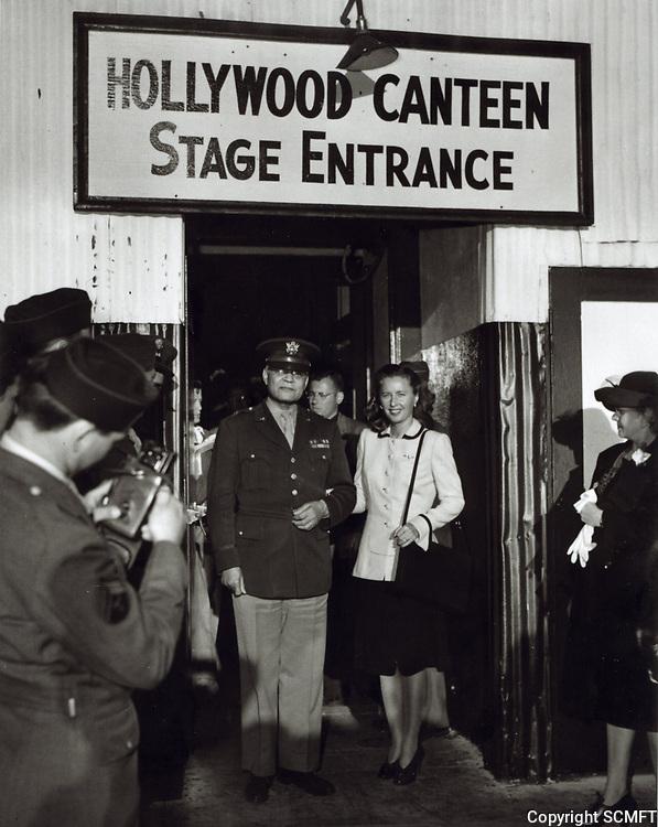 1944 Barbara Stanwick escorts a high ranking officer at the Hollywood Canteen