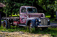 Beat up old flatbed truck sitting out in the elements.