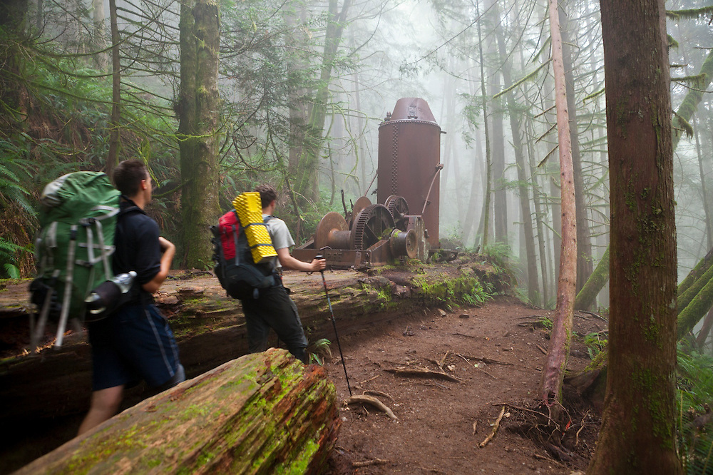 Zach Podell-Eberhard (right) and Henry pass a derelict donkey engine in a forest shrouded in mist along the West Coast Trail, British Columbia, Canada.