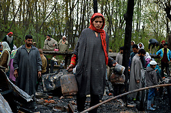 April 5, 2017 - Srinagar, Jammu and Kashmir, India - A Kashmiri women  she stands in the debris in her hand of her home that was gutted by a fire on the outskirts of Srinagar, Indian controlled Kashmir, Wednesday, April 5, 2017. Many residential houses and shanties were damaged in the fire. (Credit Image: © Zahid Hussain Bhat/Pacific Press via ZUMA Wire)