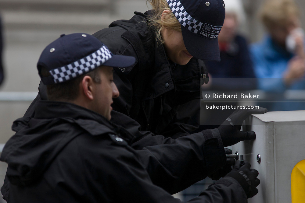 London 17/4/13 - Police officer search the street before the funeral of Margaret Thatcher. Draped in the union flag and mounted on a gun carriage, the coffin of ex-British Prime Minister Baroness Margaret Thatcher's coffin travels along Fleet Street towards St Paul's Cathedral in London, England. Afforded a ceremonial funeral with military honours, not seen since the death of Winston Churchill in 1965, family and 2,000 VIP guests (incl Queen Elizabeth) await her cortege.