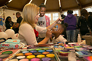 Face painting during a TRA, Tenants and residents association, community day at Cressingham Gardens rotunda on 9th September 2015 in South London, United Kingdom. Cressingham Gardens is a council garden estate, located on the southern edge of Brockwell Park. It comprises of 306 dwellings and built to the design of Lambeth Borough Council architect Edward Hollamby in the early 1970s. In 2012, Lambeth Council proposed regeneration of the estate, a decision highly opposed by many residents. Since the announcement, the highly motivated campaign group Save Cressingham Gardens has been active.