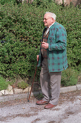 Elderly man walking outdoors using walking stick,
