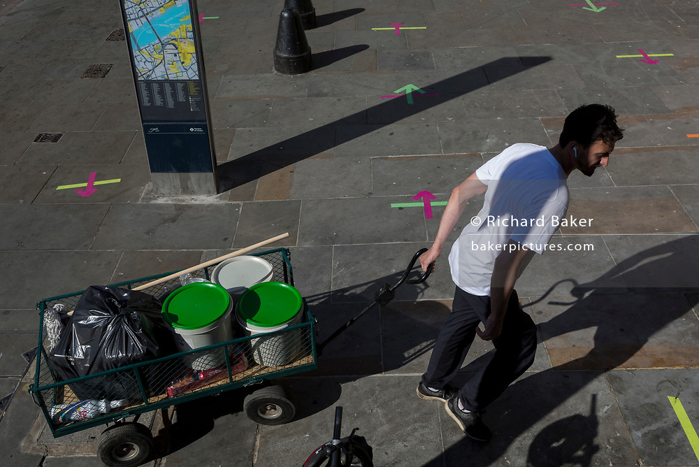 Ten weeks after the UK went into Coronavirus pandemic lockdown, the Office for National Statistics reveal that the total death toll has passed 50,000 covid-19 victims, a fast food worker pulls kitchen supplies past social distancing markings on the pavement outside a Post Office in the borough of Southwark which ensure queues of daytime customers keep to within lockdown rules, on 2nd June 2020, in London, England.