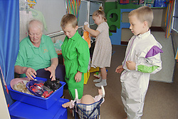 Play worker helping two boys and a girl dress up in fancy dress,