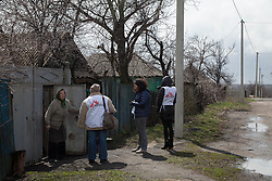 Doctor Svetlana Niekurasa greets a woman at the gate of her home in Debaltsevo as the MSF medical team makes the rounds of patients who are unable to leave their homes due to frailty, illness or old age, to attend one of the mobile clinics in the town.