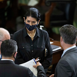 Austin, Texas USA March 9, 2021: Texas senators, including Sen. Carsol Alvarado, D-Houston confers with colleagues at a session of the 87th Texas Legislature. The first two months of the five-month session entails bill filing, committee meetings and considering emergency items requested by Governor Greg Abbott.
