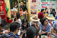 Teens eat at street-side low tables in the old quarter of Hanoi, Vietnam.
