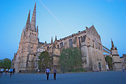 The Saint Andre Cathedral 11th 12th century with its majestic twin gothic towers in the evening at sunset on the place pey berland in Bordeaux, people walking on the square city Bordeaux Gironde Aquitaine France