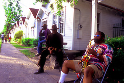 Stock photo of three men sitting on the sidewalk in the afternoon, one playing a saxophone