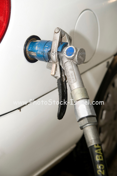 compressed natural gas vehicle with fuel filler hose at a petrol station