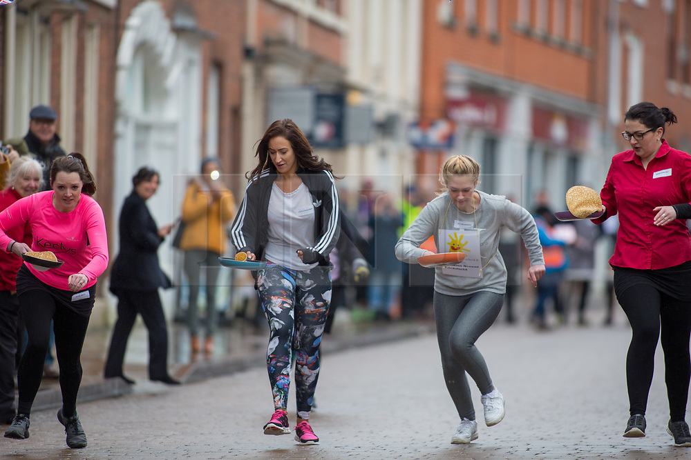 © Licensed to London News Pictures. 13/02/2018. The three hundredth (300) run of the annual Shrove Tuesday Pancake race took place in the centre of Lichfield. The race has run uninterrupted even through both world wars. Pictured, the ladies heats. Photo credit: Dave Warren/LNP