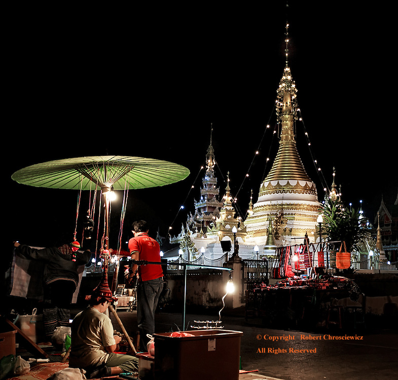 Night Market: The Buddhist temples form the background for the remnants of the night market as the vendors pack their goods away, Wat Chong Kham and Wat Chong Klang, Mae Hong Son Thailand.