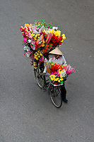 Bicycle overflowing with colourful flowers on the streets of Hanoi.