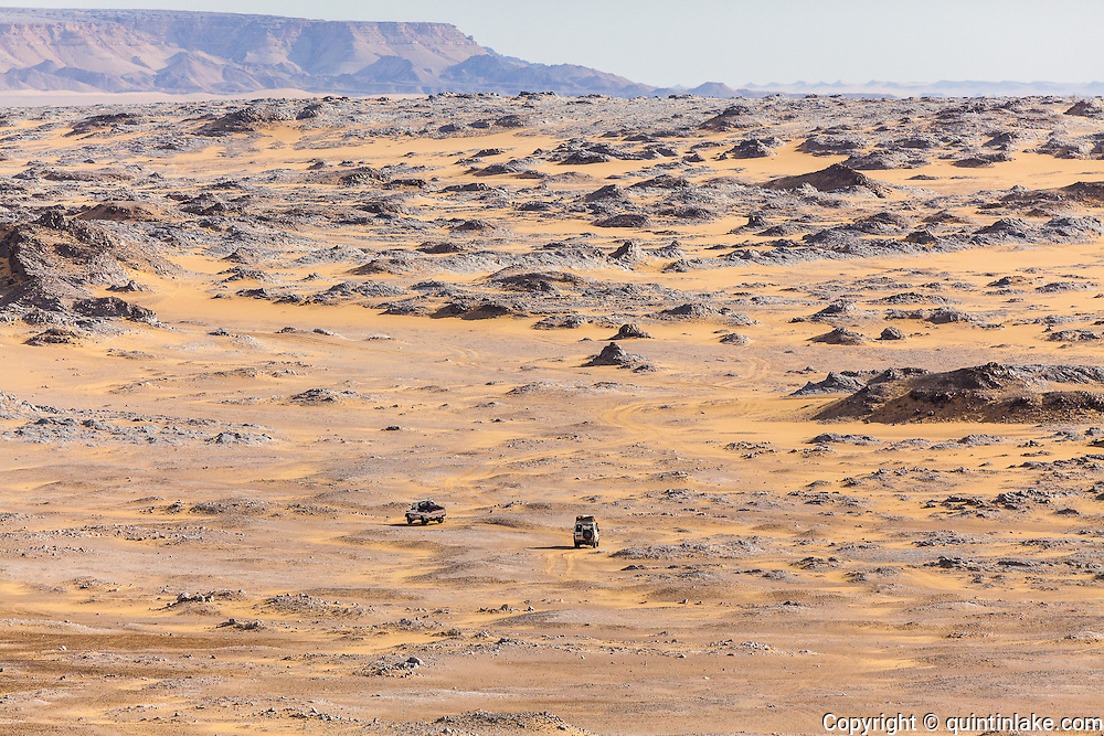 Two landcruisers pick their way through the rugged landscape at the edge of the Sahara Suda (Black Desert), Egypt