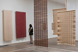 """© Licensed to London News Pictures. 09/10/2018. LONDON, UK. A visitor views (L) """"Drapery material woven for Rena Rosenthal's Madison Avenue store"""", 1935, and (R) """"Free hanging room dividers"""", 1949, all by Anni Albers.  Preview of the UK's first exhibition of works by German artist Anni Albers at Tate Modern who used the ancient art of hand-weaving to produce works of modern art.  Over 350 of her artworks from major collections from Europe and the US are on show 11 October to 27 January 2019.  Photo credit: Stephen Chung/LNP"""