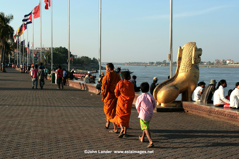 Monks strolling the riverfront along Sisowath Quay which is lined with dozens of restaurants and bars offering curbside seating and a range of hotels and guesthouses, some with riverside views.