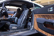 """New York, NY - 1 April 2015. A detail of the door and driver's seat of a Rolls Royce Wraith in the """"Inspired by Film"""" package.  The vehicle sports doors hinged at the rear, called by Rolls """"coach doors,"""" but popularly referred to as """"suicide doors."""""""