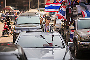"""15 JANUARY 2014 - BANGKOK, THAILAND: An anti-government protestor stands in the sunroof of her Mercedes Benz and waves Thai flags during an anti-government motorcade in Bangkok. Tens of thousands of Thai anti-government protestors continued to block the streets of Bangkok Wednesday to shut down the Thai capitol. The protest, """"Shutdown Bangkok,"""" is expected to last at least a week. Shutdown Bangkok is organized by People's Democratic Reform Committee (PRDC). It's a continuation of protests that started in early November. There have been shootings almost every night at different protests sites around Bangkok. The malls in Bangkok are still open but many other businesses are closed and mass transit is swamped with both protestors and people who had to use mass transit because the roads were blocked.    PHOTO BY JACK KURTZ"""