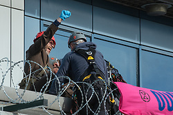 © Licensed to London News Pictures. 10/10/2019. London, UK. An Extinction Rebellion protester holds his fist up on the roof of the main entrance to London City Airport as he is fitted with specialist climbing equipment by police officers as they prepare to remove him. Photo credit: Peter Manning/LNP