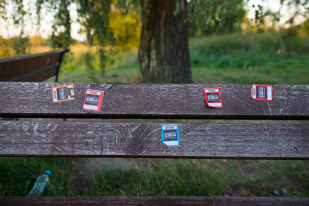 Stickers for tours in various languages are left by visitors on a bench at a bus stop outside Auschwitz II–Birkenau, part of the infamous network of concentration and extermination camps operated by Germany during WWII in the town of Oświęcim, Poland, and elsewhere in Europe.