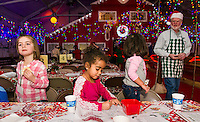 Coloring and cookies for Ella, Dulce and Luna before they go in to visit Santa and Mrs. Claus in their North Pole Workshop at Christmas Village Thursday evening.  (Karen Bobotas/for the Laconia Daily Sun)