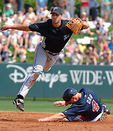 Toronto Blue Jays shortstop Jason Smith, left, flies through the air after forcing out Atlanta Braves' Pete Orr and throwing to first base to complete a double play on Kelly Johnson during the third inning of their spring training baseball game in Lake Buena Vista, Florida.