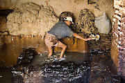 A man cleans wool pulled from sheep skins in the tanning pits at the Berber leather tannery in Fes El-Bali, Morocco.