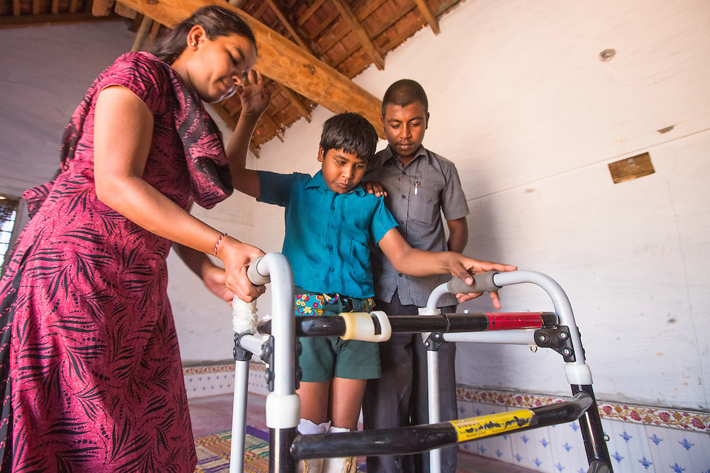 CAPTION: Under the Chamkol programme, every disabled member of the community has an Individual Health Plan (IHP). For Rajashekar, who has cerebral palsy, this means following a tailor-made exercise regime. During regular visits to his home, Rehabilitation Therapy Assistant (RTA) Sudha shows his family how to support him with this. LOCATION: Marialla (village), Kasaba (hobli), Chamrajnagar (district), Karnataka (state), India. INDIVIDUAL(S) PHOTOGRAPHED: From left to right: Sudhamani R., Rajashekar and Rangaswamy.