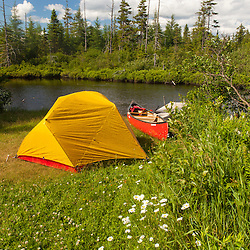 """Tent and canoe next to the Cold Stream """"deadwater"""" above Upper Cold Stream Falls in Maine's Northern Forest. Johnson Mountain Township."""