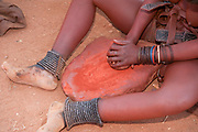 Himba woman crushes red clay, This is then used to coat their hair. Photographed in a Himba village, Epupa Falls, Kaokoland, Namibia, Africa
