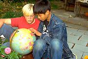 Cambodian/American and friend age 13 studying  globe.  St Paul Minnesota USA