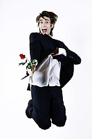 studio shot portrait of a young funny expressive thin and tall man on isolated background jumping holding a rose