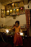 Young girl with sparklers in front of a shrine. The annual Huttari harvest celebrations are the main event of the year of the locals of Madikeri and Coorg. Coorg or Kadagu is the largest coffee growing region of India, in the state of Karnataka, the inhabitants - the Kodavas have been cultivating crops such as coffee, black pepper and cardamon for many generations.