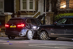 **Incident reported to be connected with the death of Multi-millionaire hotelier Sir Richard Sutton in Dorset**<br /> © Licensed to London News Pictures. 08/04/2021. London, UK. A police vehicle (L) and the offenders vehicle (R) on Chiswick High Road following a incident in which a vehicle was stopped by armed police at approximately 22:30hrs on Wednesday 07/04/2021 when police approached the vehicle, officers discovered the lone male occupant had sustained a number of serious self-inflicted injuries. . Photo credit: Peter Manning/LNP
