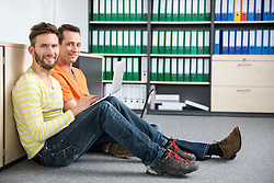 Two young men office sitting floor relaxed