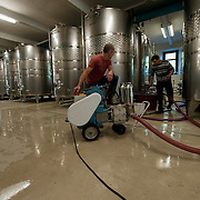 VARNA, ITALY - OCTOBER 13: Workers prepare yeast mixture in the moder cellar at Abbazia di Novacella on October 13, 2010 in Varna, Italy. Abbazia di Novacella, in Alto Adige established in the year 1142 by Augustinian monks, is one of the oldest vineries in the world; it has a production of about 400,000 bottles of world class wines including Kerner, Sylvaner, Pinot Grigio, Gewurztraminer.
