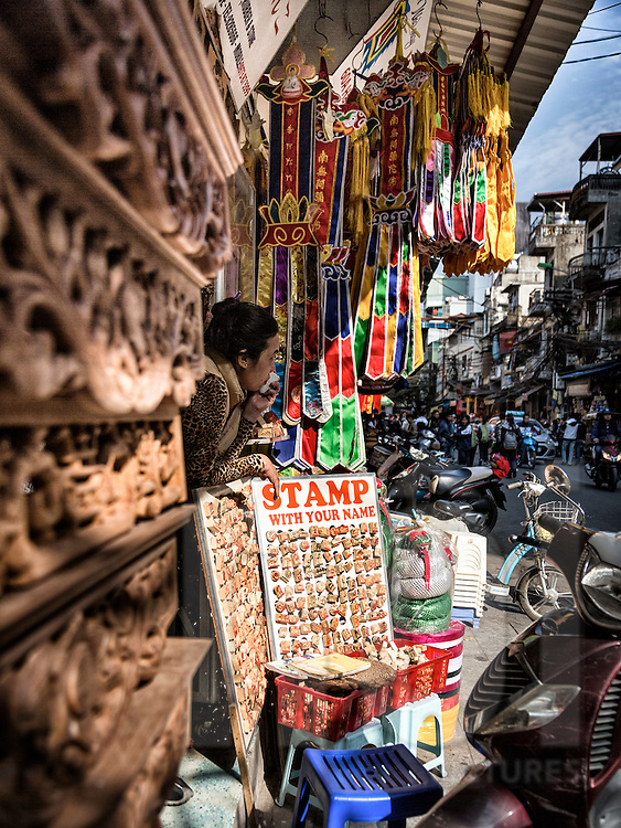 Seller leans out of her stamp shop along Hang Quat street in Hanoi's Old Quarter, Vietnam, Southeast Asia