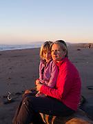 A mother and daughter enjoy sunset on the beach at Hokitika, New Zealand.
