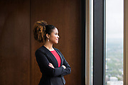 African American lawyer looking out the window of her office building in Denver, Colorado.