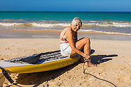 Older woman putting on leash for Stand Up Paddle Boarding, Kailua Beach, Oahu, Hawaii ****Model Release available