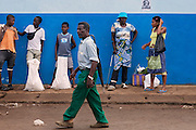 A man carrying an umbrella on his shoulder is walking near a market on the island of Sao Tome, Sao Tome and Principe, (STP) a former Portuguese colony in the Gulf of Guinea, West Africa.