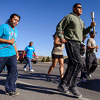 052714       Cable Hoover<br /> <br /> Gallup Police officer Jared Yazzie carries the Special Olympics torch during the first running leg of the torch run in Gallup Tuesday.
