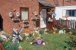 Front garden in modern house with windmills; ornaments and flowers,