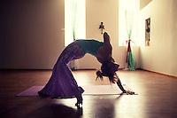Woman artfully practicing the heart felt yoga pose Wild Thing in a moody studio atmosphere. AKA CAMATKARASANA