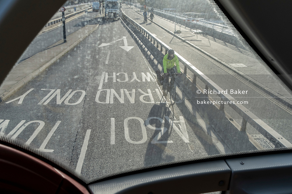 Seen from the rear of a London bus, a cyclist wearing a hi-viz jacket rides northwards across Waterloo Bridge towards Westminster, on 1st December 2020, in London, England.