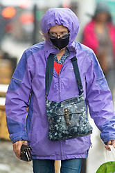 ©Licensed to London News Pictures 19/08/2020             Sevenoaks, UK. A lady wearing a purple waterproof. Wet weather across large parts of the UK today as shoppers in Sevenoaks High Street, Sevenoaks, Kent get their umbrellas out. The Met office has issued a severe weather warning for 70mph winds over the next two days. Photo credit: Grant Falvey/LNP